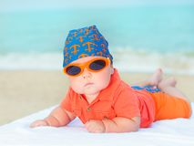 Baby on the beach. Cute baby laying on the sunbed at the beach Stock Image