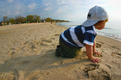 Baby on beach looking out to sea. Toddler boy on hands and knees in sand looking towards the water Stock Photography