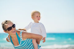 Baby on beach piggybacking mother Royalty Free Stock Image