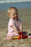 Baby beach play. A little caucasian white blond baby with cute and happy facial expression sitting in the sand and playing with her toys on the beach having Stock Photo