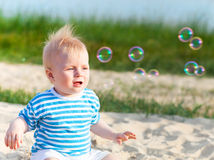 Baby on the beach playing with soap bubbles Royalty Free Stock Photo