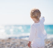 Baby on beach pointing into distance. Baby girl on beach pointing into distance Stock Photos