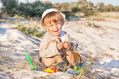Baby is at the beach with sand dunes. Royalty Free Stock Image