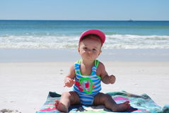 Baby in the beach. Baby sitting on a beach towel on the background of the ocean royalty free stock images