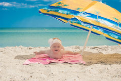 Baby on a beach under the umbrella. Cure baby laying on the sunbed under umbrella at the beach of Black sea Stock Image