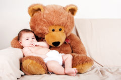 Baby with bear. Cute Caucasian Hispanic unisex baby in arms of a big brown stuffed teddy bear sitting on couch