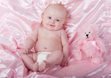 Baby and bear. A baby girl on a pink blanket with a teddy bear stock photography