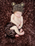 Baby with bear hat portrait. Newborn baby sleeping while wearing brown bear hat stock photography