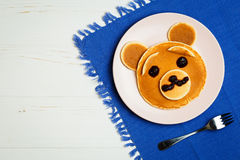 Baby bear on a pink plate. Baby pancakes in a pink plate on a blue towel with space for text Stock Image