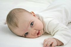 Baby in bed. Blue eyed baby smiling in bed royalty free stock image