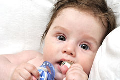 Baby in bed with dummy and silver toy. On pillow Royalty Free Stock Image