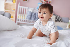 Baby in the bed. Smiling baby boy crawling on the bed Royalty Free Stock Photo