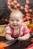 Baby on bed. Smiling baby looking at camera under a dack bedding Royalty Free Stock Photo