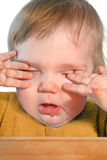 Baby bed time. Cute very tired baby rubbing eyes with his/her hands Stock Photo