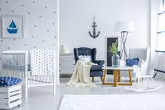 Baby bedroom with dotted wall. White baby bedroom with painting hanging on the dotted wall and two armchairs by small table Stock Images