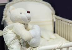 Baby bedroom with white teddy bear. On the bed royalty free stock images