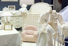 Baby bedroom with white teddy bear. And dresses on the chair royalty free stock images