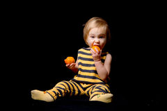 Baby-bee eating oranges. Funny baby dressed as a bee eating an orange on black background royalty free stock image