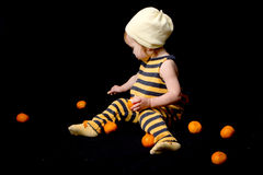 Baby-bee with tangerines. Funny baby dressed as a bee sitting among oranges on black background royalty free stock photo