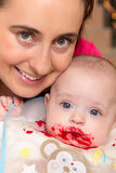 Baby with beetroot on his mouth. In his mother's arms Stock Images