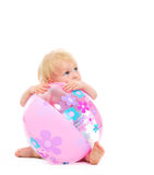 Baby behind beach ball looking on copy space. Isolated on white royalty free stock photo
