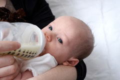 A baby being bottle fed Stock Image