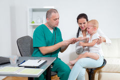 Baby being checked by a doctor Stock Photos