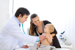 Baby being checked by doctor using stethoscope Stock Images