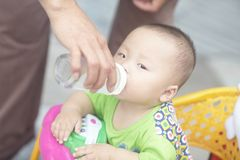 Baby being fed. Baby boy being fed by adult royalty free stock photos