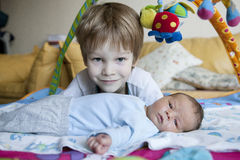 Baby being held tenderly by big brother Stock Image
