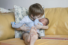 Baby being held tenderly by big brother Royalty Free Stock Images