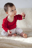 Baby with bell. Portrait of a baby in a red top sitting on sheep skin ringing a small bell Royalty Free Stock Photos
