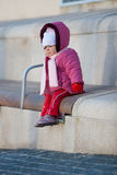 Baby on a bench. Picture of a baby girl sitting on a wooden bench Stock Images