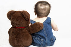 Baby and Best Friend Teddy. Cute baby picture of baby boy sitting next to his best friend Teddy Bear Royalty Free Stock Photo