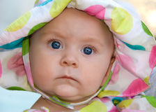 Baby with Big Blue Eyes. A young baby with big beautiful blue yes stares at you Royalty Free Stock Image