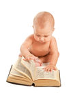 Baby with big book sitting on the floor Stock Images