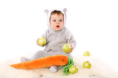 Baby with big carrot and apples Stock Images