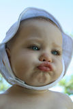 Baby with big cheeks. Baby girl with big cheeks and a white hat stock photos