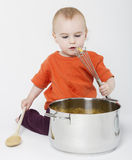 Baby with big cooking pot. On neutral grey background Stock Photos