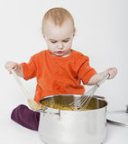 Baby with big cooking pot. On neutral grey background Royalty Free Stock Photography