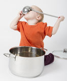 Baby with big cooking pot. On grey background Stock Images