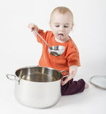 Baby with big cooking pot. On neutral background Royalty Free Stock Image