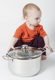 Baby with big cooking pot. Isolated on grey background Royalty Free Stock Images