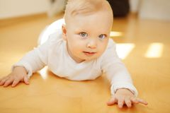 Baby with big eyes in crawlers lies on wooden floor. Adorable baby with big light eyes and blond hair in white crawlers lies on wooden floor with calm face Stock Images
