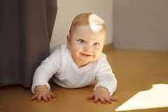 Baby with big eyes in crawlers lies on wooden floor. Adorable baby with big light eyes and blond hair in white crawlers lies on wooden floor with calm face Royalty Free Stock Photo