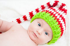 Baby With Big Eyes Wearing Cute Knit Hat. Baby wearing red white and green striped knit hat Royalty Free Stock Photos