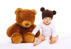 Baby with big teddy bear toy on white Stock Images