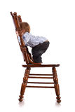 Baby on a big wooden chair in a studio. isolated Stock Image