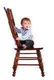 Baby on a big wooden chair in a studio. isolated Royalty Free Stock Images