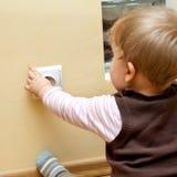 Baby bij elektrische contactdoos Stock Foto